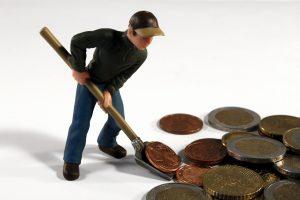A imagem mostra uma pessoa juntando moedas gigantes com uma pá